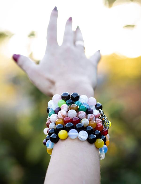 Edelstein Armbänder an einer Hand und die Sonne im Hintergrund