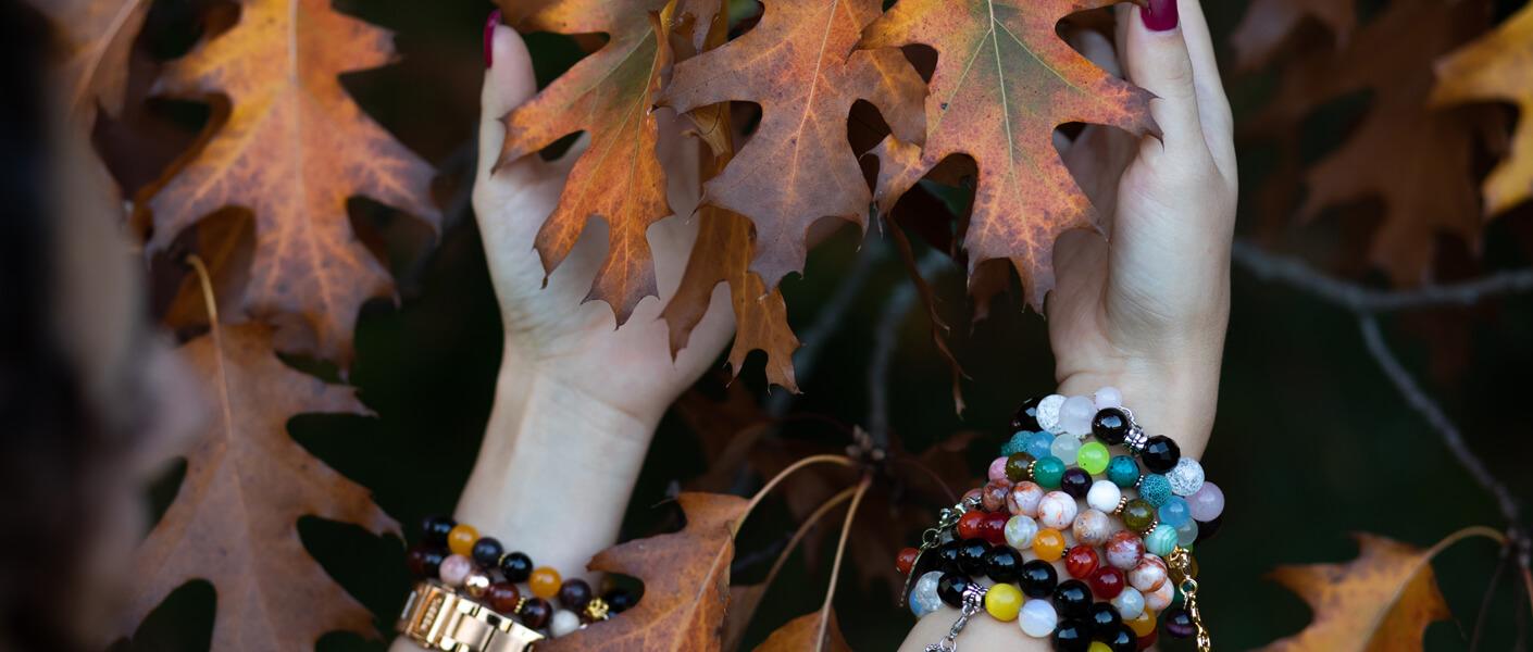 Hände mit Edelsteinarmbändern im Herbst