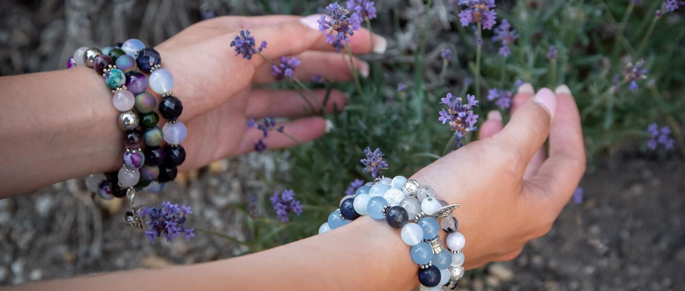 Hände mit blau-lilanen Armbändern