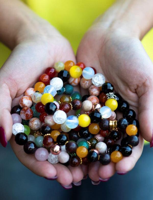 Mehrere verschiedene Armbänder in den beiden Händen